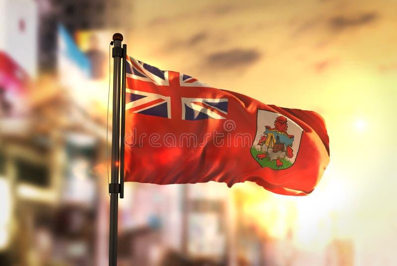 反对城市被弄脏的背景的百慕大旗子在日出Backligh 免版税库存照片