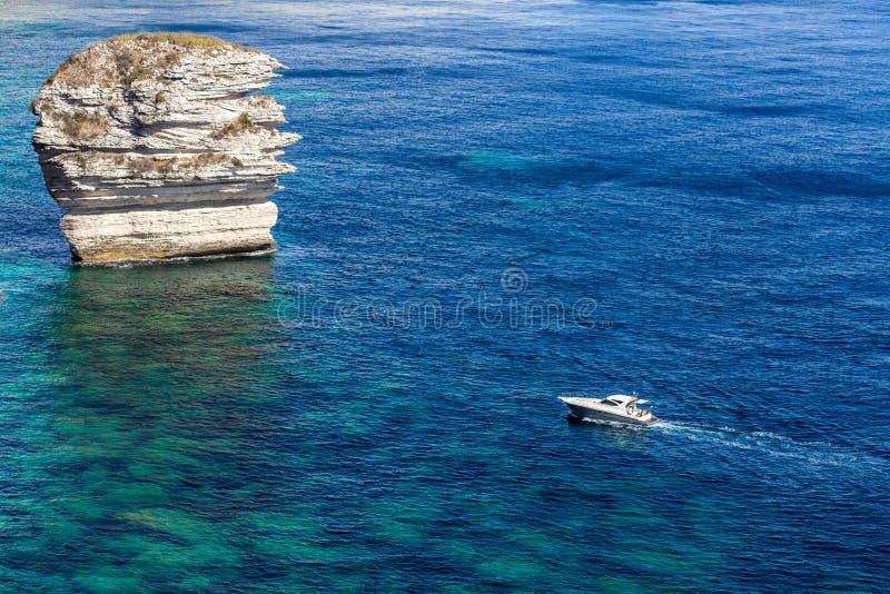 反对堆岩石的汽艇 库存图片