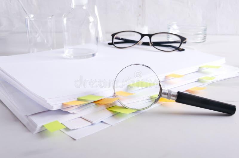 反对堆文件,医疗玻璃器皿,在白色实验室书桌上的玻璃的放大器 免版税库存图片