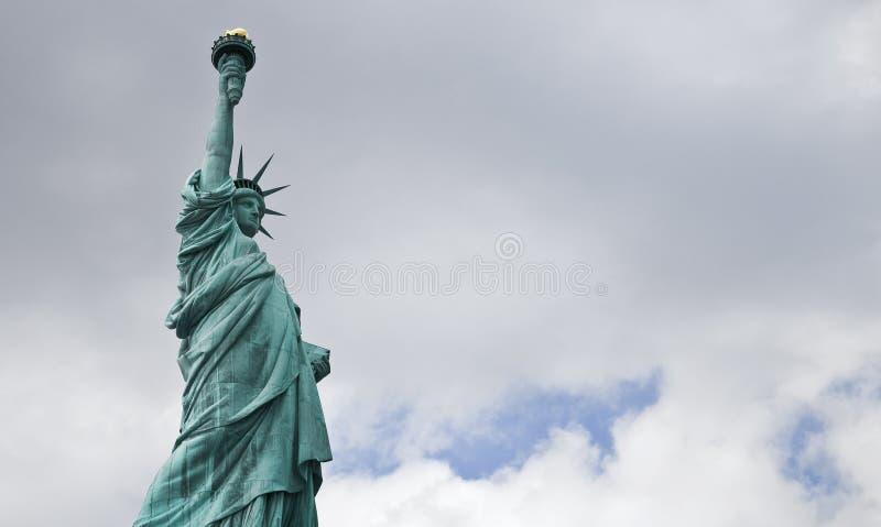 反对多云天空的自由女神像 免版税库存图片