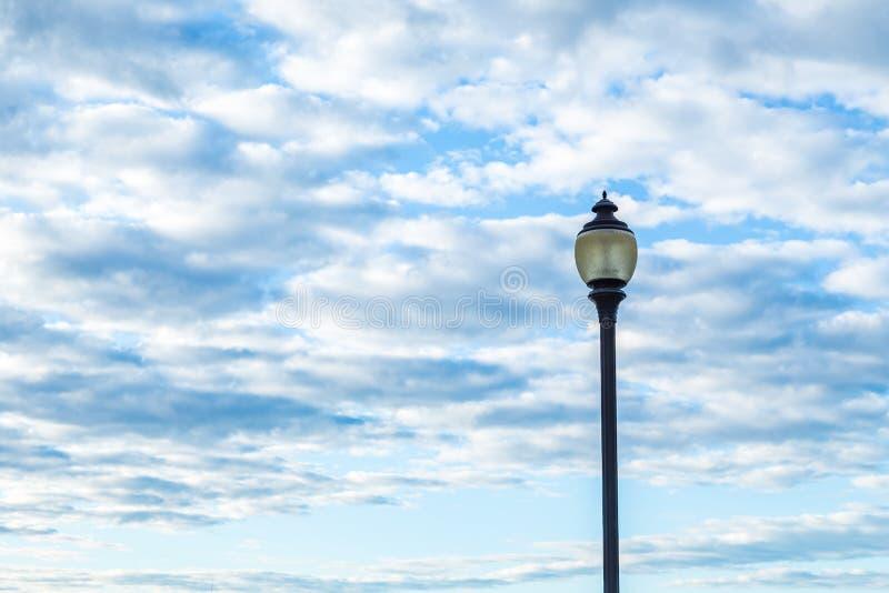 反对多云天空的路灯柱 免版税图库摄影