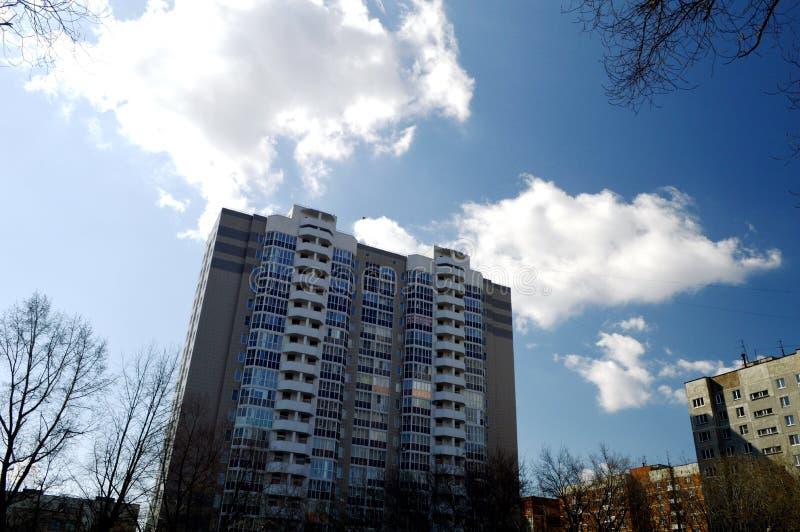 反对多云天空背景的高层建筑物 库存图片