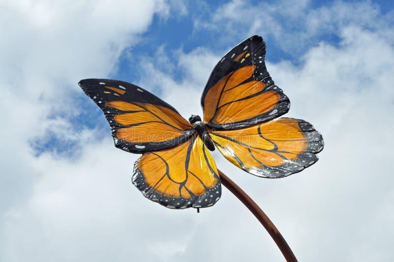反对多云蓝天的蝴蝶模型 免版税库存照片