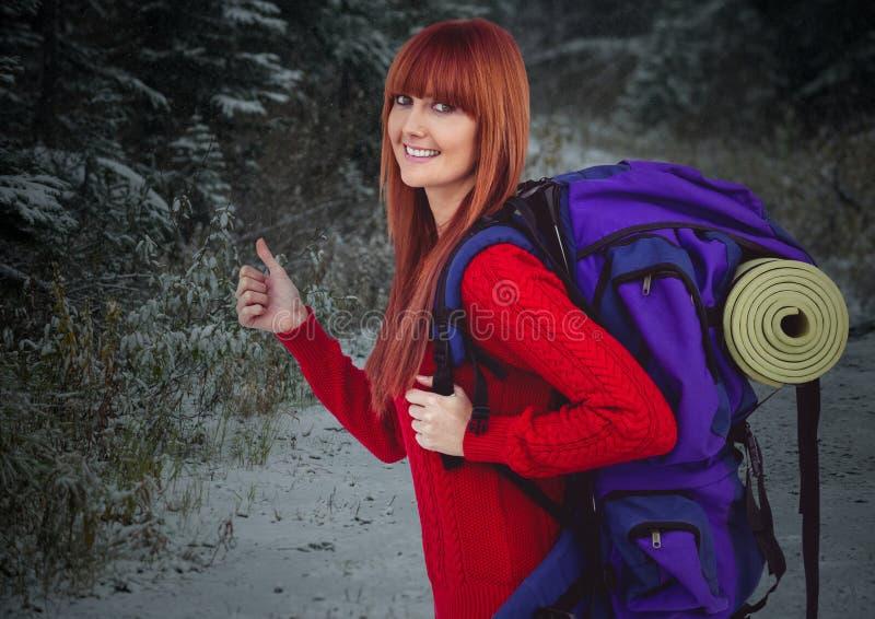 反对多雪的森林的千福年的背包徒步旅行者赞许 图库摄影