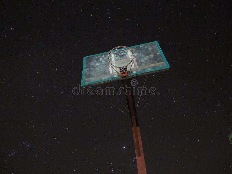 反对夜间天空的篮球篮 图库摄影