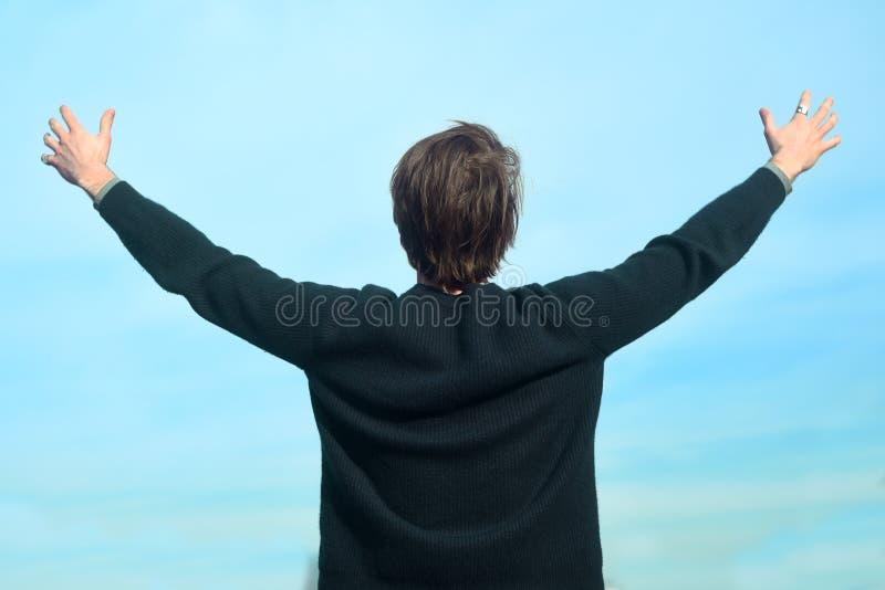 反对天空的一个人站立并且享有生活 一个人享受好天气 人提高了他的手和笑 库存图片