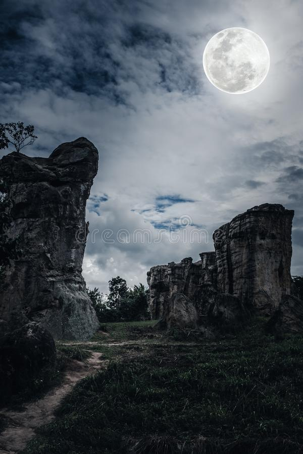 反对天空的冰砾与云彩和美丽的满月在附近 免版税库存图片