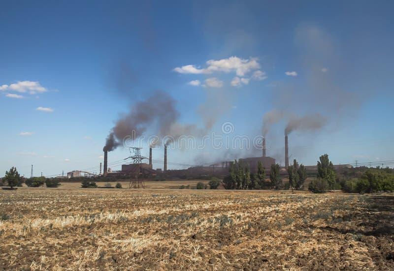 反对天空蔚蓝和云彩的抽烟的工厂管子 免版税库存照片