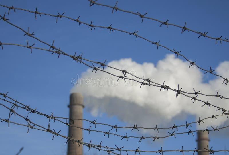 反对天空蔚蓝和烟斗的铁丝网底视图 环境问题,生态题材 库存图片