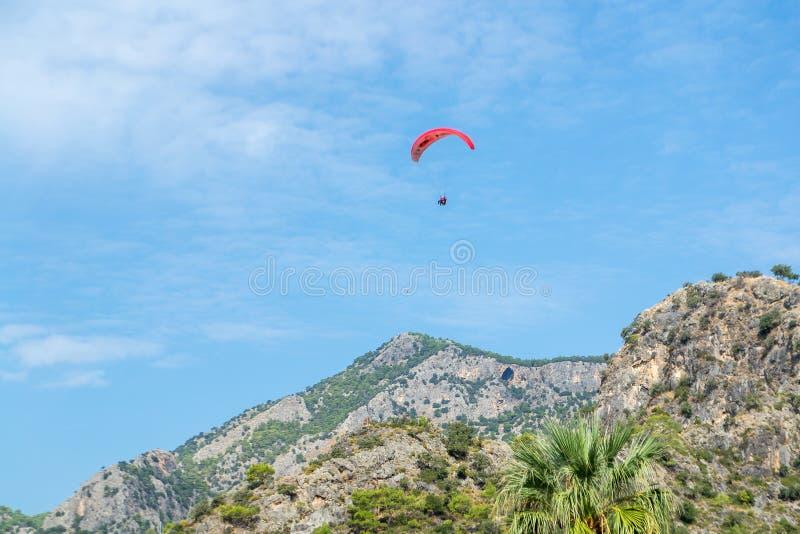 反对天空蔚蓝和美丽的山的跳伞运动员 一张五颜六色的夏天明信片的背景 免版税图库摄影