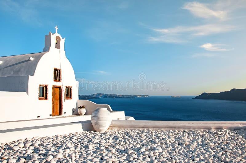 反对天空蔚蓝和蓝色爱琴海的美丽的老白色教会 Oia,圣托里尼,希腊,欧洲 经典白色希腊语 库存图片