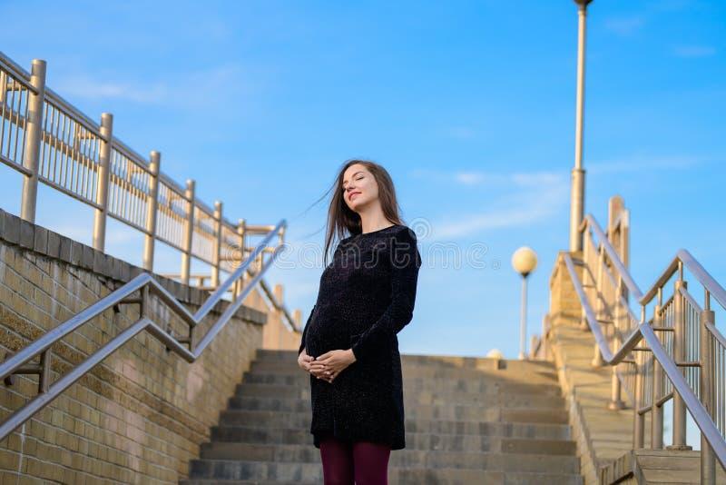 反对天空蔚蓝的孕妇 一年轻孕妇的画象反对一清楚的天空蔚蓝的,都市怀孕,美好和 免版税库存图片