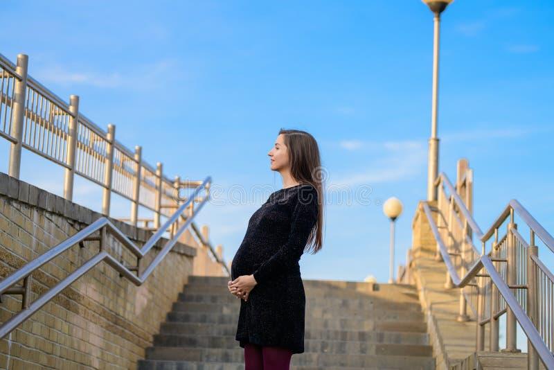 反对天空蔚蓝的孕妇 一年轻孕妇的画象反对一清楚的天空蔚蓝的,都市怀孕,美好和 免版税库存照片