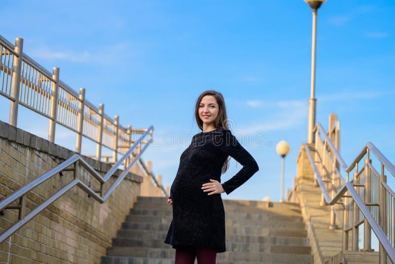 反对天空蔚蓝的孕妇 一年轻孕妇的画象反对一清楚的天空蔚蓝的,都市怀孕,美好和 免版税图库摄影