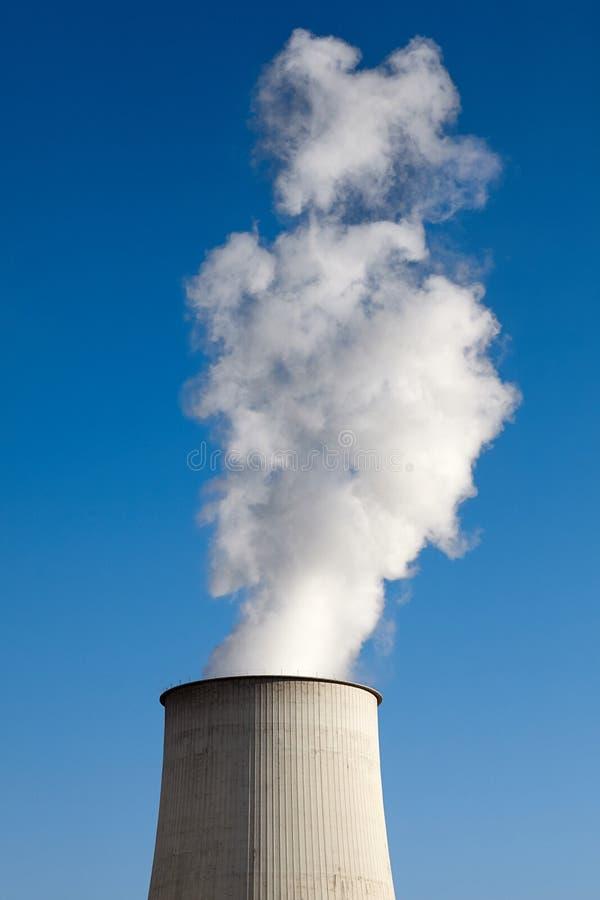 反对天空蔚蓝的抽烟的烟囱 免版税库存照片