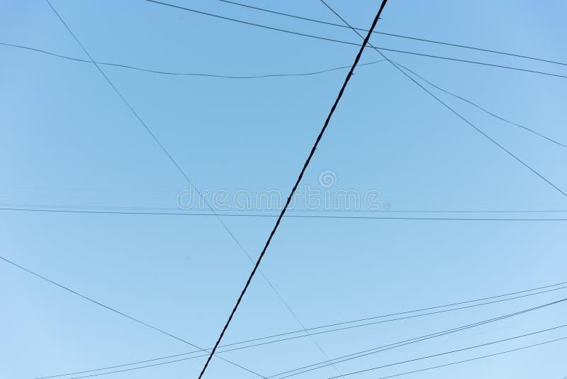 反对天空蔚蓝的抽象相交的导线 免版税库存照片