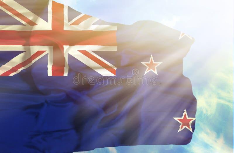 反对天空蔚蓝的新西兰挥动的旗子与阳光 免版税库存图片