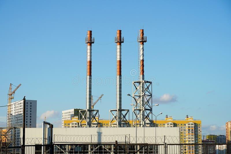 反对天空蔚蓝的管子连续 白色气体加热管子,在没有烟的一个城市 库存照片