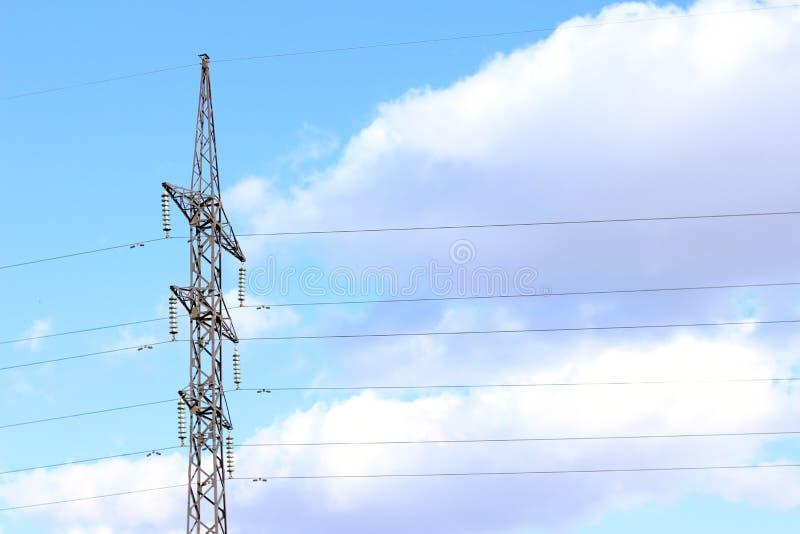 反对天空蔚蓝的输电线与云彩发电站导线 库存照片