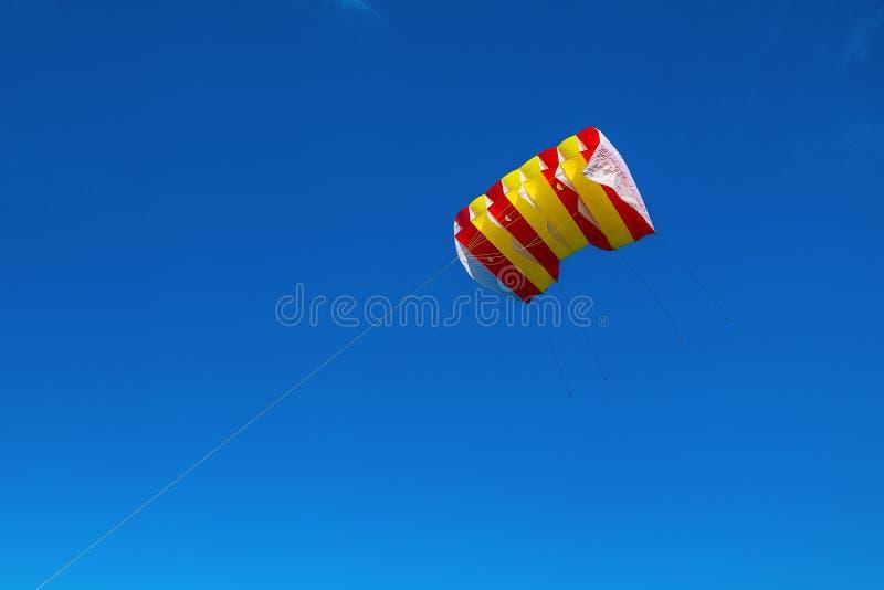 反对天空蔚蓝的黄色,白色和红色镶边风筝飞行 免版税图库摄影