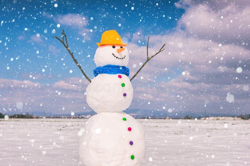 反对天空蔚蓝背景与落的雪花,愉快的冬天的逗人喜爱的微笑的雪人 免版税图库摄影