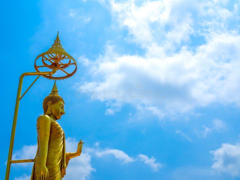 反对天空蔚蓝背景的站立的菩萨雕象 免版税库存图片