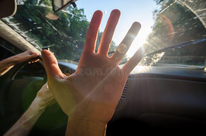 反对太阳的年轻手在有聚焦的汽车 免版税库存照片