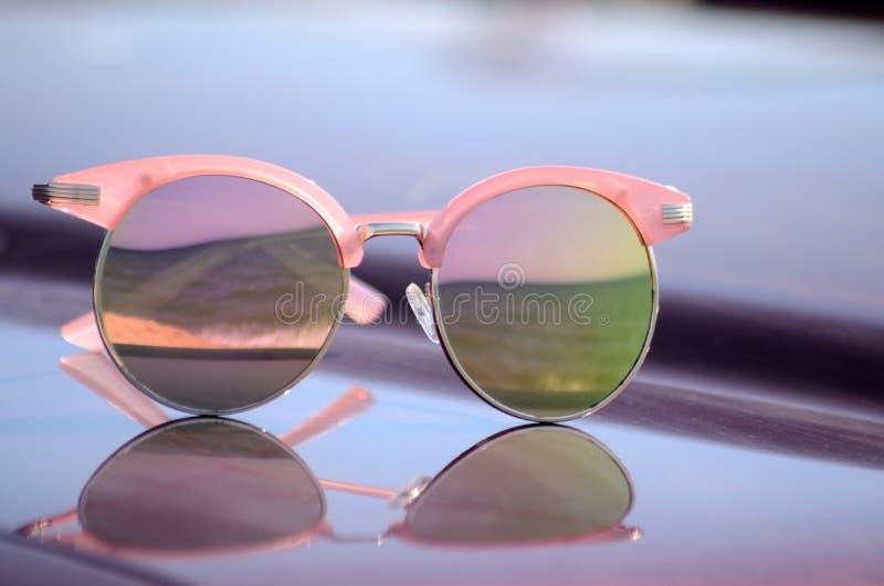 反对太阳的桃红色太阳镜在汽车的敞篷 免版税库存照片