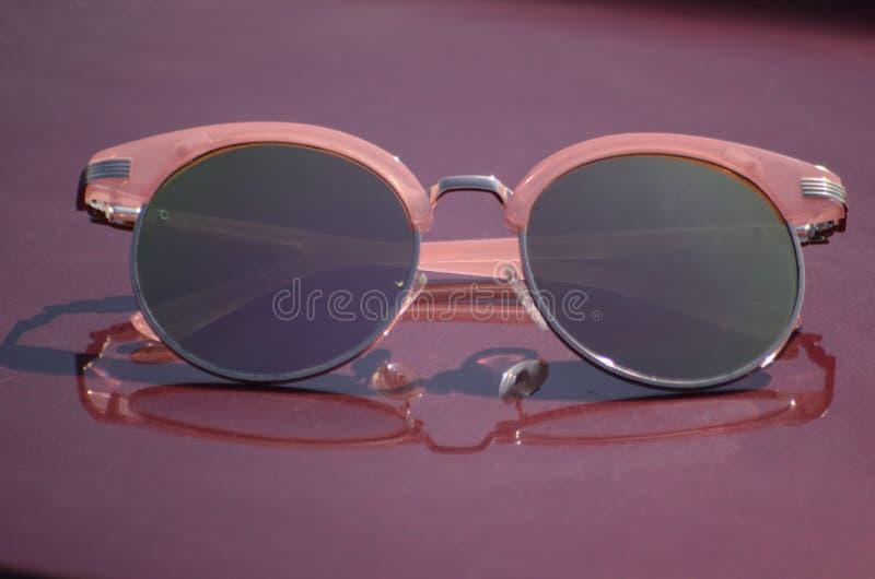 反对太阳的桃红色太阳镜在汽车的敞篷 图库摄影