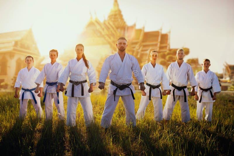 反对寺庙的男性和女性空手道小组 免版税库存照片