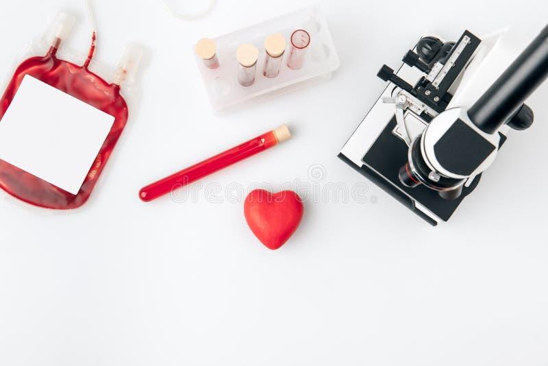 反对小瓶的红色心脏有血液和显微镜的 免版税图库摄影