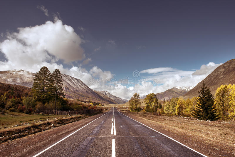 反对山和多云天空的老高速公路 库存照片