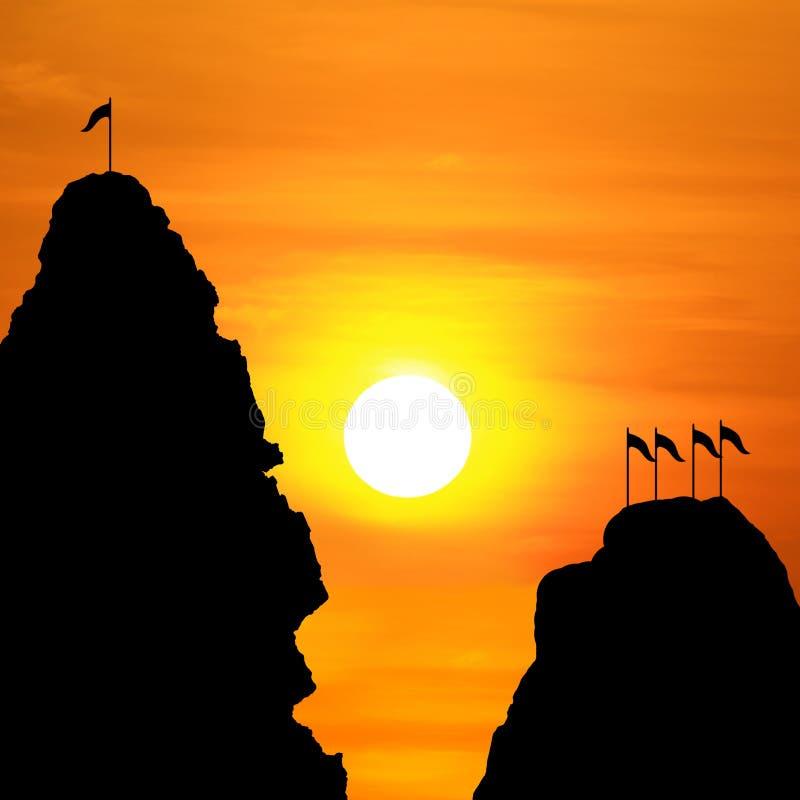 反对峭壁山和旗子的背景的剪影在峰顶在一个晚上日落 库存图片