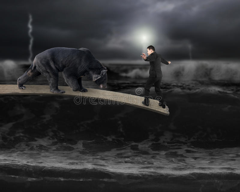 反对平衡在与黑暗的风雨如磐的oce的板条的熊的商人 免版税库存图片