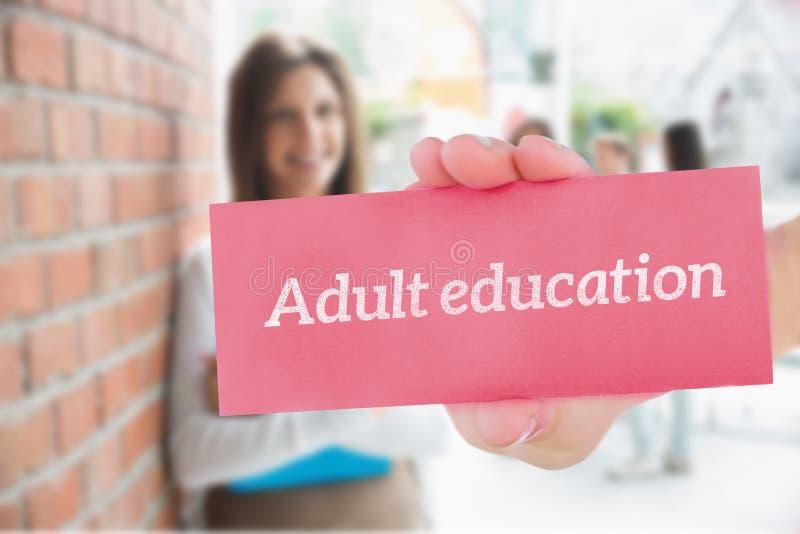 反对微笑和拿着笔记薄的俏丽的学生的成人教育 免版税库存照片