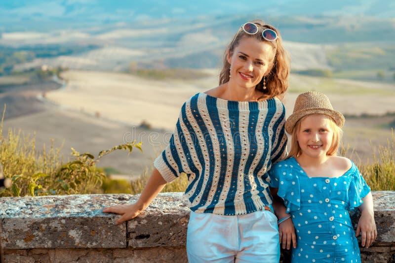 反对托斯卡纳的风景的愉快的母亲和儿童游人 库存图片