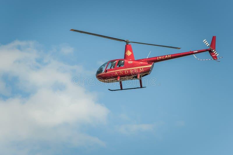 反对执行在airshow的天空蔚蓝的红色直升机 库存图片