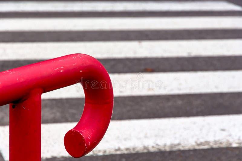 反对斑马线的红色栏杆 库存图片