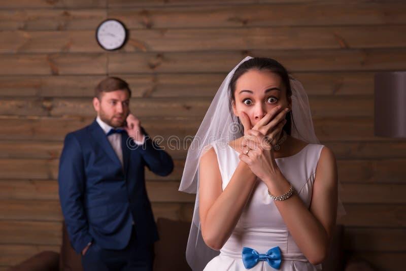 反对新郎的惊奇的新娘谈话在电话 免版税库存图片