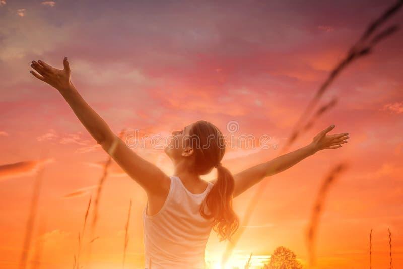 反对日落天空的自由和愉快的妇女 库存照片