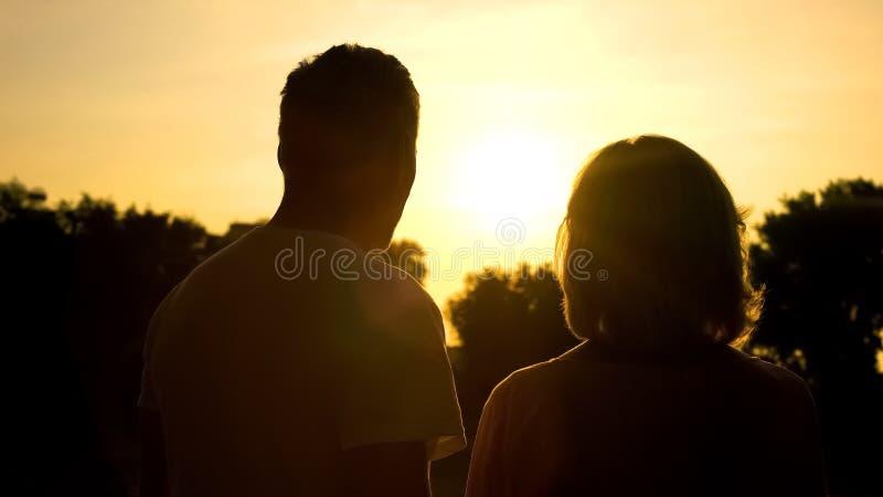 反对日落背景,联系幸福,爱的老男人和妇女阴影 免版税库存图片