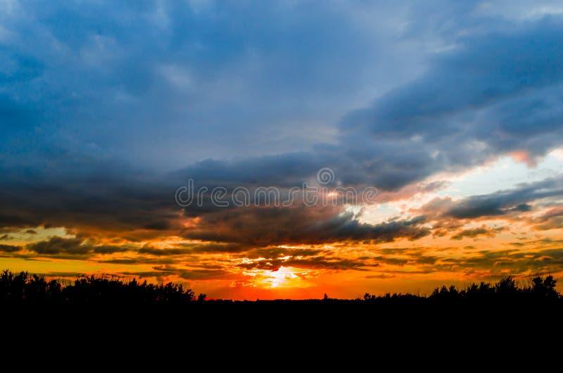 反对明亮的蓝天的暴风云,日落 免版税库存图片
