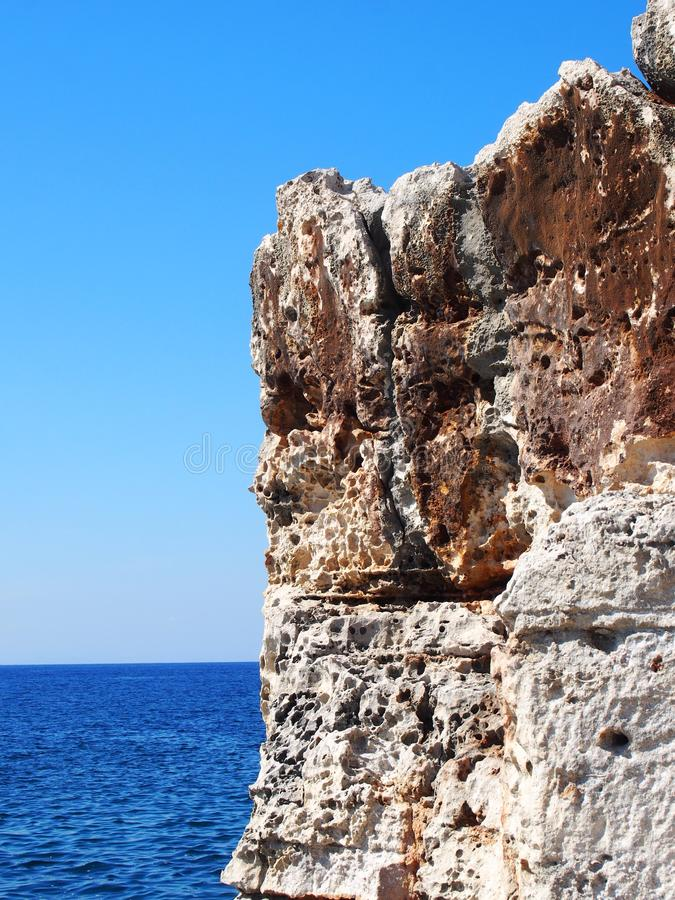 反对明亮的蓝色被日光照射了天空和海的粗砺的接合的岩石露出 免版税库存照片