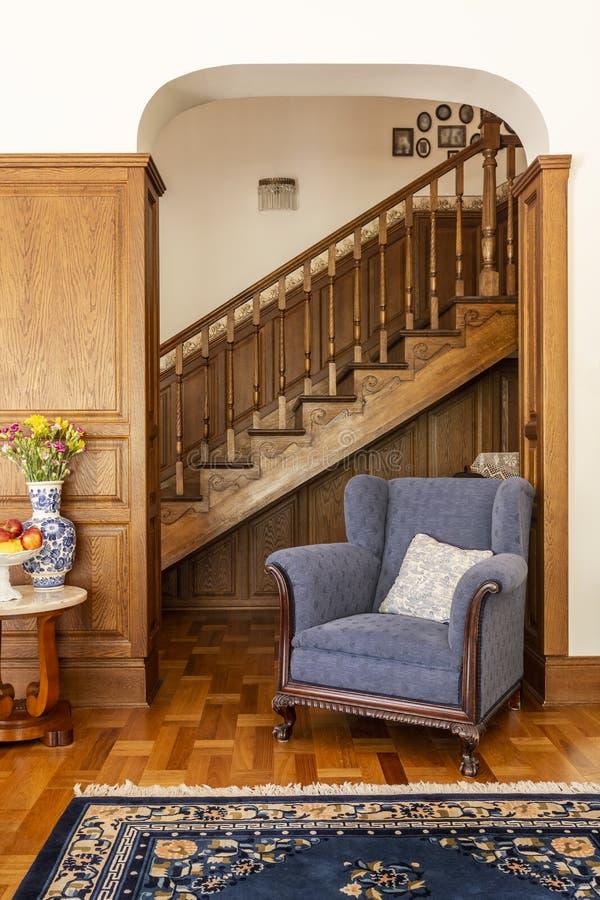 反对木台阶的蓝色扶手椅子在相互经典的客厅 库存照片