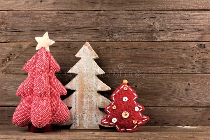 反对木头的三棵破旧的别致的圣诞树 库存照片