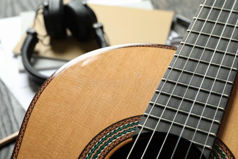 反对木背景的经典吉他和音乐制造商辅助部件 库存照片