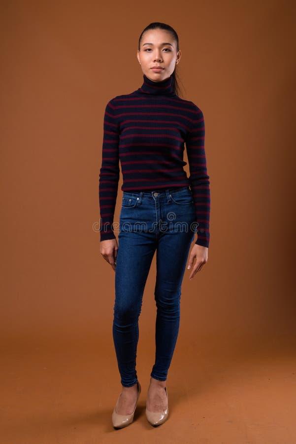 反对棕色背景的年轻美丽的亚裔变性妇女 免版税库存照片