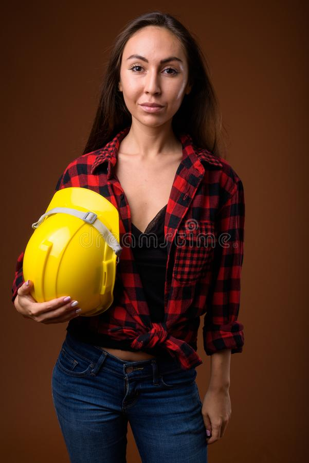 反对棕色backgrou的年轻美丽的妇女建筑工人 免版税库存图片