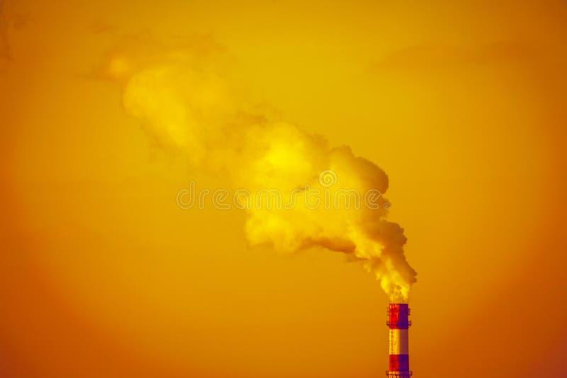 反对橙色天空的工业管子 免版税库存图片