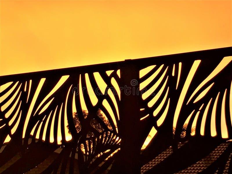 反对橙色天空的篱芭剪影 免版税库存图片